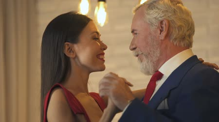 perguntando : Young woman flirting and dancing with old millionaire on date, escort service