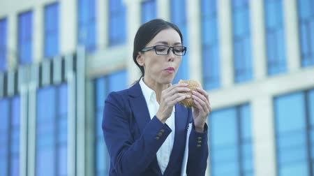 быстрый : Lady in business suit eating unhealthy burger during lunchtime, stressful job Стоковые видеозаписи