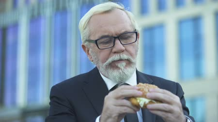 restauration rapide : Senior male in suit eating burger pendant le déjeuner, debout près de office center Vidéos Libres De Droits