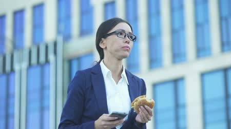 colesterol : Female office manager eating unhealthy burger checking messages on phone. Stock Footage