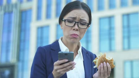 internar : Young female manager eating unhealthy burger in hurry, checking news on phone Stock Footage