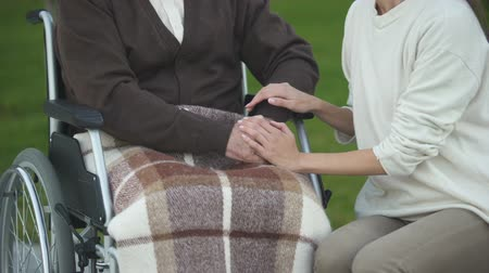 traumatic : Young lady stroking senior male hands, family support and care, loving relative Stock Footage