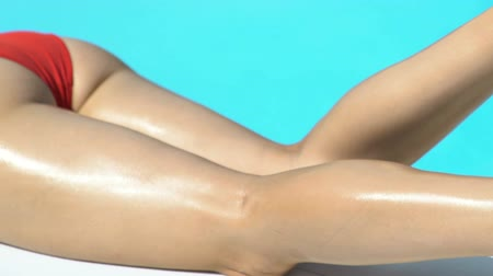 curtimento : Sexy woman  legs moving, sunscreen lotion on skin, sunbathing near pool Stock Footage
