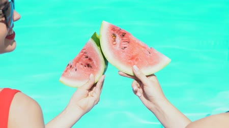 simultaneously : Smiling women clinking watermelon slices and laughing near pool.