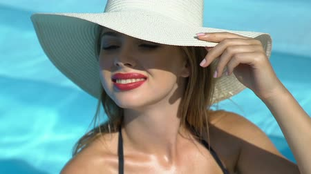 sunhat : Rich woman in big white hat standing in pool, luxury resort hotel.