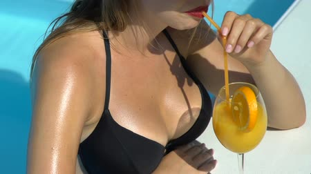 sunhat : Woman in bikini sunbathing and drinking cocktail near pool, sunscreen lotion