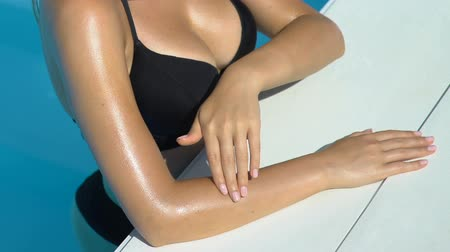 lotion : Lady in bikini stroking skin, using sunscreen lotion, resting in swimming pool