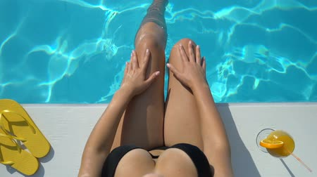 mladé ženy : Womans legs playing with water in swimming pool, top view, enjoying vacation