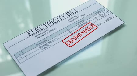 účty : Electricity bill second notice, hand stamping seal on document, payment.