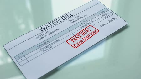 účty : Past due water bill, hand stamping seal on document, payment for services