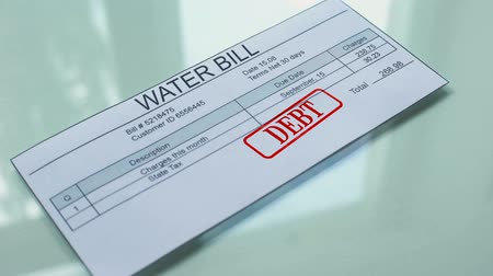 makbuz : Water bill debt, hand stamping seal on document, payment for services, tariff Stok Video