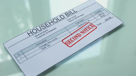 maliyet : Household bill second notice, hand stamping seal on document, payment.