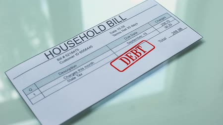 factuur : Household bill debt, hand stamping seal on document, payment for services Stockvideo