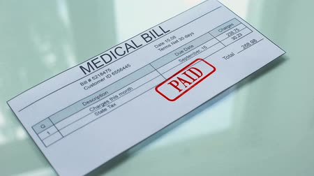 утверждение : Medical bill paid, hand stamping seal on document, payment for services, tariff