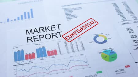 weekly : Market report confidential, hand stamping seal on official document, statistics