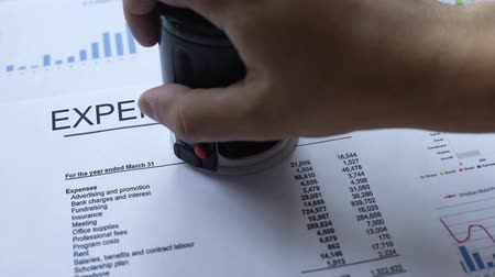 banking document : Expense report approved, hand stamping seal on official document, statistics