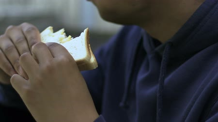 canteen : Lonely teenager eating sandwich in school canteen, outsider, racial problem Stock Footage