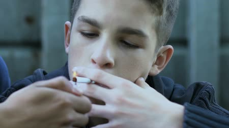 schoolkid : Teenager lighting cigarette to classmate, peers pressure, youth bad habits Stock Footage