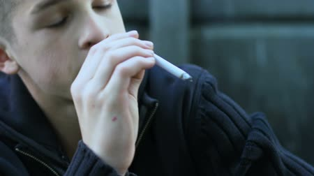 harmful habit : Teenagers smoking one cigarette for two, peers pressure to bad habits, closeup Stock Footage