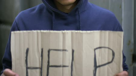 perguntando : Poor mixed-raced boy holding cardboard asking for help, social problems violence