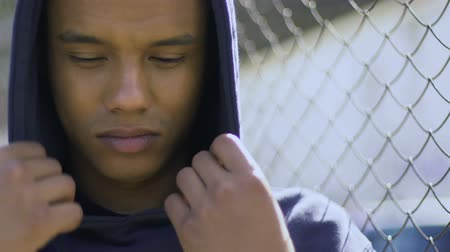 haklar : Mixed-raced boy wrapping in hood staying alone, suffering from bullying.