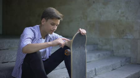 хулиган : Sad lonely skater sitting alone with skateboard, bullying problem, teenager Стоковые видеозаписи