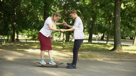longboard : Teen male teaching girl to skateboard, riding awkwardly, youth and hobbies Stock Footage