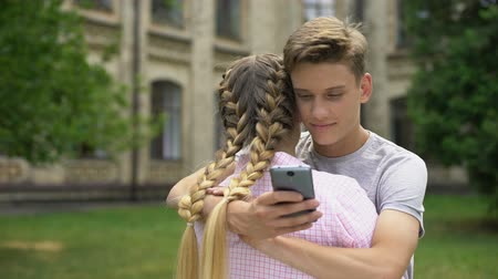 sigilo : Teenager using cell phone while hugging boyfriend, absorbed by social networks