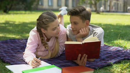 relacje : Teens hiding behind book and kissing, lying on plaid in park, first relations