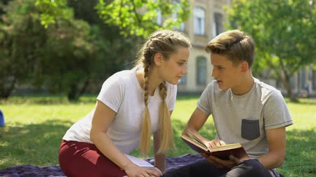refusing : Teen girl makes attempt to kiss boy, young man choosing study, disappointment Stock Footage