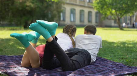 resting : Teenagers legs in similar comfortable socks, lying on plaid in park.