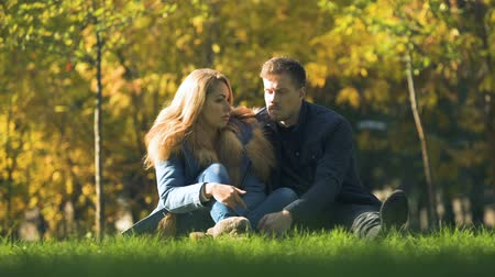 dificuldade : Serious couple speaking in autumn park sitting on plaid, discussing relationship