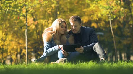 autumn discounts : Couple shopping online, using tablet at autumn park, buying warm clothes in net