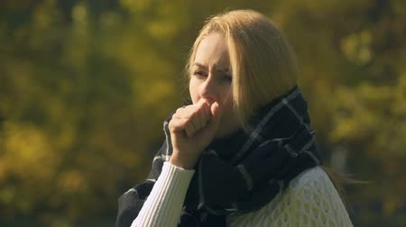 kaszel : Sick woman in scarf coughing and sneezing in autumn park, caught cold, immunity