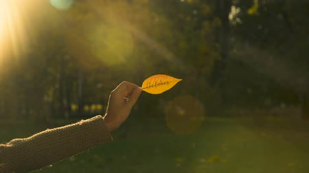 escrito : October written on autumn leaf, hand holding writings, bright golden fall season