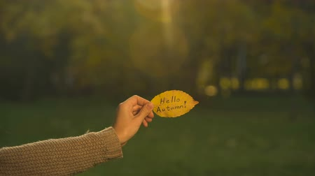 hónapokban : Hello autumn written on yellow leaf, hand holding writings, bright golden season