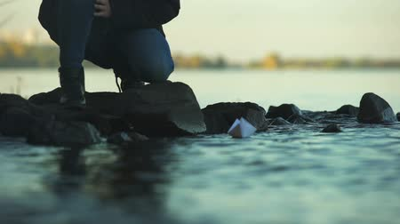remembering : Male putting paper boat on water, goodbying past, psychological therapy, closeup Stock Footage