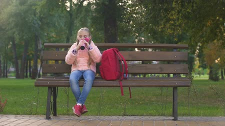 закалки : Happy schoolgirl with rucksack drinking tea from thermos cup as sitting on bench