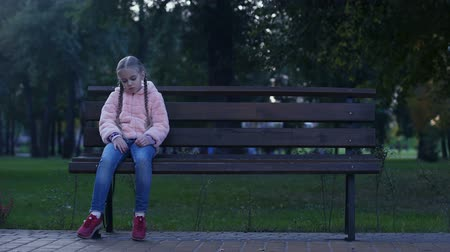 výraz : Sad school girl sitting on bench in park, lost missing kid, waiting for parents