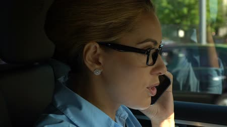 businesslady : Businesswoman driving car and talking on smartphone, overjoying about promotion Stock Footage