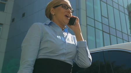 businesslady : Emotional lady talking on phone with business partner, rejoicing successful deal