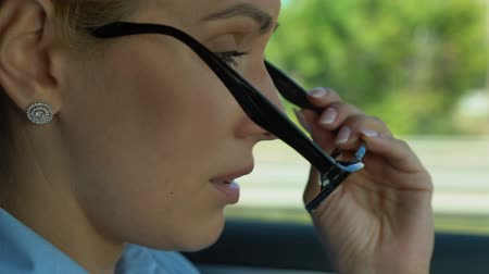prawo jazdy : Female putting on glasses while driving, worries about problems at work, stress