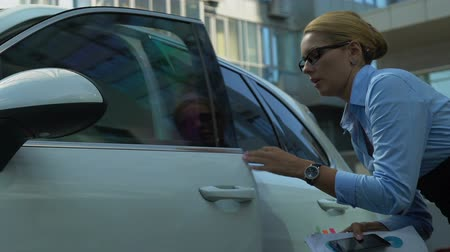 etyka : Busy female hastily getting out of auto, holding documents, hurrying to office