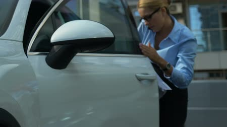piada : Clumsy business woman getting out of auto, throwing papers, bad day at work