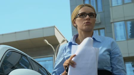 unlucky : Secretary getting out of car, dropping phone and documents, bad day beginning Stock Footage
