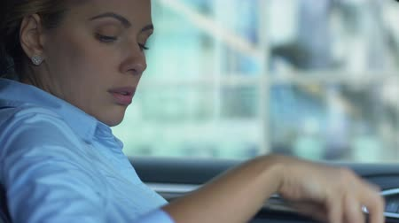 licenziamento : Tired woman sitting in automobile, exhausted after hard working day, overworked Filmati Stock