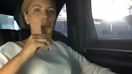 pezsgő : Pleased rich businesswoman drinking champagne on car back seat, successful deal