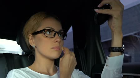 reaching : Businesslady checking her makeup and hairstyle, sitting on automobile back seat Stock Footage