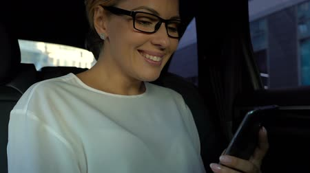 aprovado : Successful lady reading good-news message on cellphone during car drive, joy Vídeos