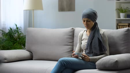 radiation therapy : Tired young woman with cancer sitting at home and drinking tea, remission